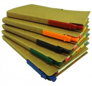 Bloco de anotação com post-its coloridos e caneta, material reciclado.